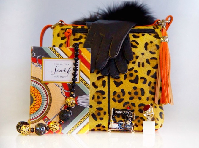 Products (left to right) are Orange/Leopard Bag $259.00; Scarf Book $29.95; Black and Gold Necklace $120.00; Black Gloves $65.00; French Brooch $115.00; and Red Ring: $80.00.