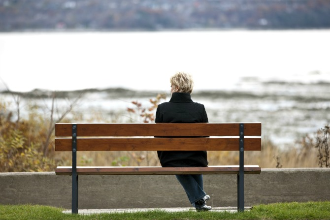 woman sitting on bench sad feature
