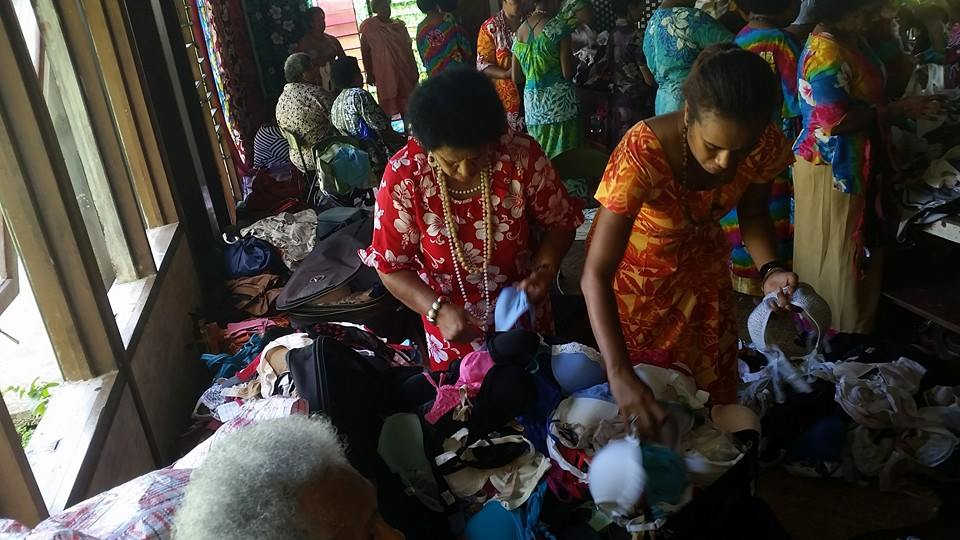 Women sorting through donated bras in Fiji uplift project