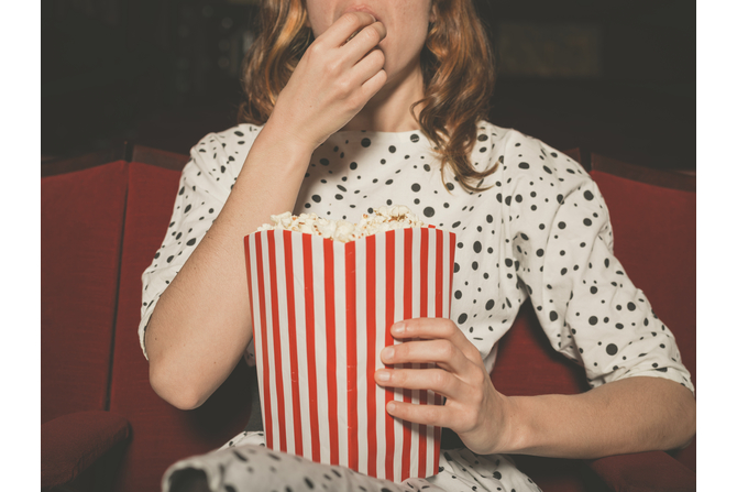 Woman eating popcorn while watching a movie