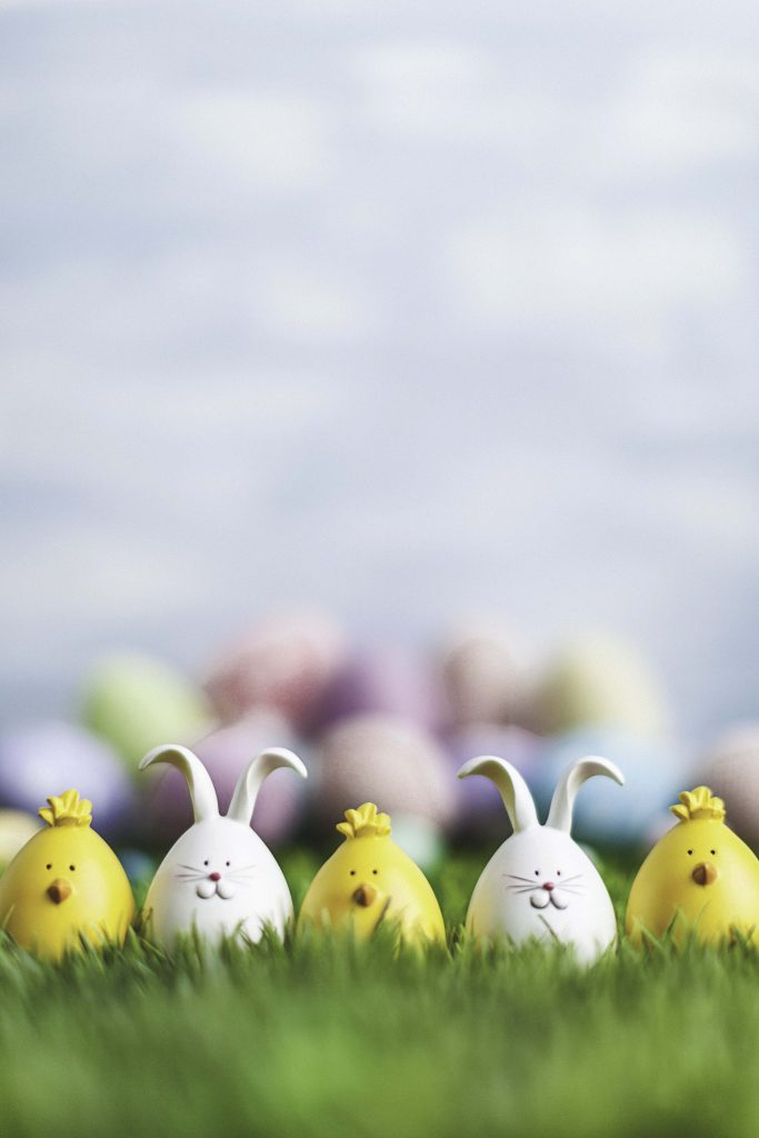 Little Easter critters sitting in grass with Easter egg background