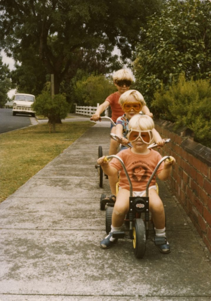 Three Children in Goggles Riding Bikes on Footpath, Brighton East