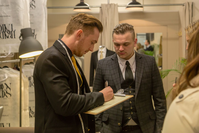 Braddon Tailors' staff consults with a client. Photo: Jonathon McFeat.