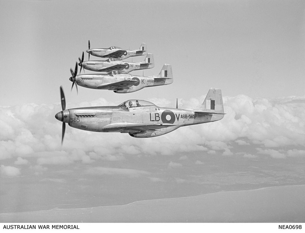 Flying from Townsville, Qld. 1945-07-27. Four P-51 Mustang aircraft of No. 84 Squadron RAAF, newest fighter to be flown by Australians in this theatre of war, flying in echelon right, up formation. Pilots and aircraft, front to rear: 290898 Squadron Leader J. A. Cox of Mt Lawley, WA, in aircraft A68-565, coded LB-V a North American P-51K-10-NT; 404355 Flight Lieutenant (Flt Lt) R. G. Riddel of Galloways Hill, Qld, in aircraft A68-529 coded LB-K; 402530 F Lt D. N. McQueen of Grafton, NSW, in aircraft A68-526 coded LB-W; 411111 Flt Lt S. E. Armstrong of Charleville, Qld, in aircraft A68-523 coded LB-0.