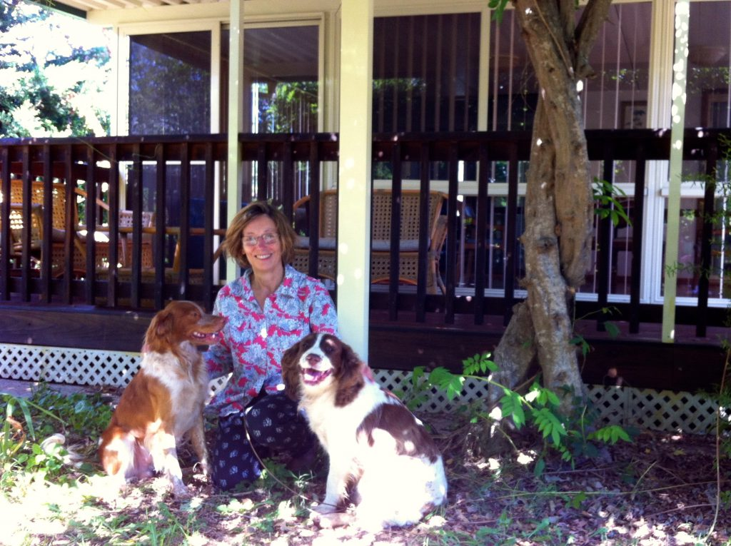 Louisa and her Springer Spaniel, Tilba, and Brittany Spaniel, Merry, under the wisteria at Cockatoo House