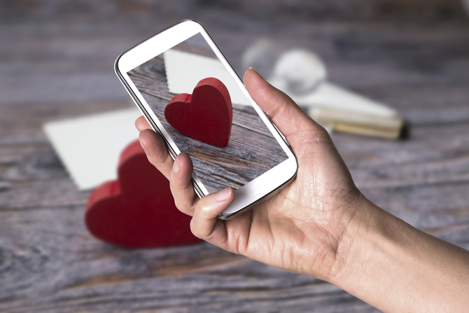 Closeup of hand holding smartphone taking picture of red heart