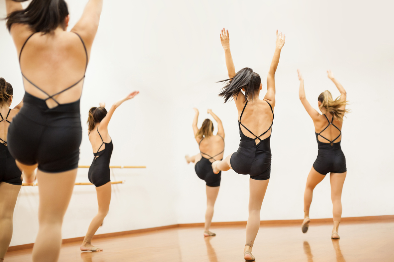 Full length view of a group of women in leotards practicing a dance routing together, seen from behind