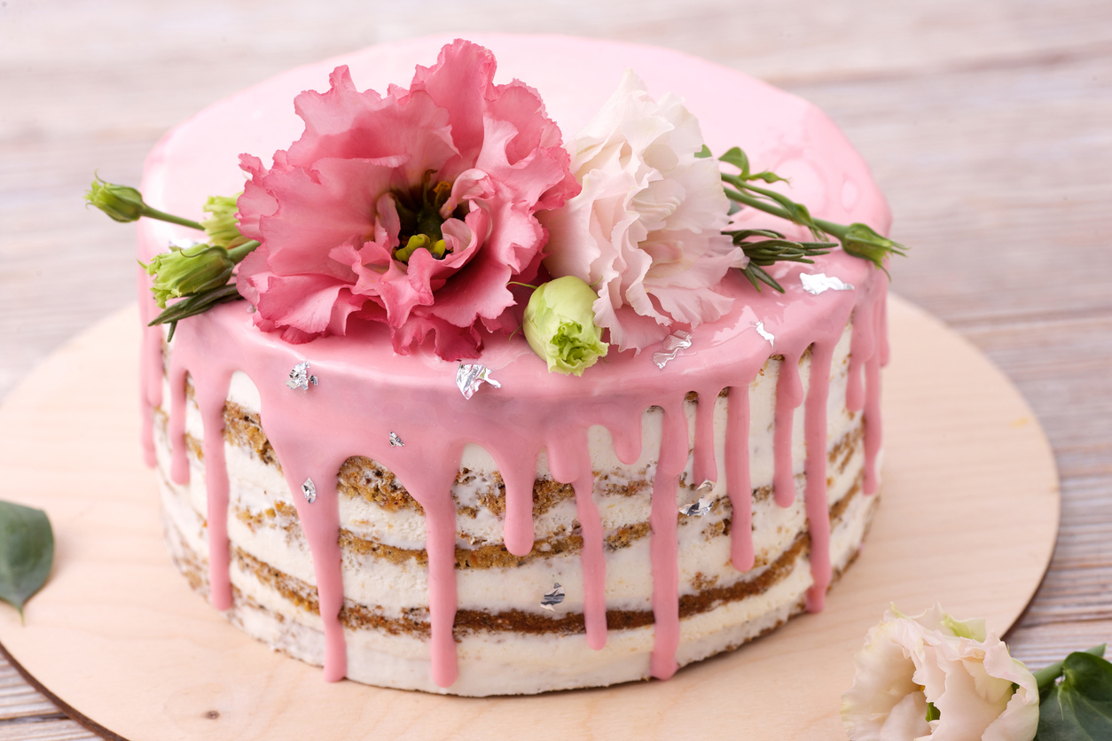 Carrot cake with pink glaze, beautiful flowers and edible silver as a decoration